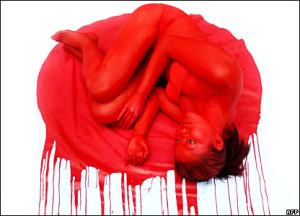 Image depicts a woman in a fetal position drenched in fake blood.