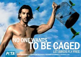 Indian Bollywood actor freeing birds. He is shown giving direct eye contact to the camera and displaying his power and strength.