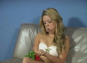 A white woman stuffing radishes into her mouth with painfully stretched cheeks.