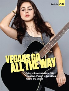 16 year old girl is posed provocatively with her hand in her hair, lips parted, legs slightly spread. She is wearing a tight fitting gray tanktop and tight black pants. She also has a guitar over her shoulder.