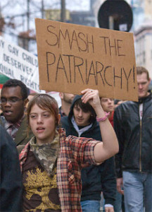 "Female protester holding cardboard sign that reads: ""Smash the Patriarchy!"""