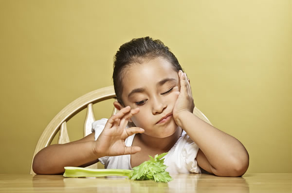 Unhappy kid picking at a piece of celery