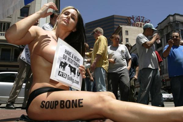 "Woman sitting on street holding PETA sign. She is naked except for underwear. ""SOUP BONE"" is written along her thigh. Men are gathered around her, one is taking a picture with his cellphone."
