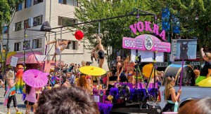 Parade float with many women in underwear and lingerie dancing on poles. A kitten adoption group.