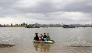 Filipino women cling to wreckage in rising waters.