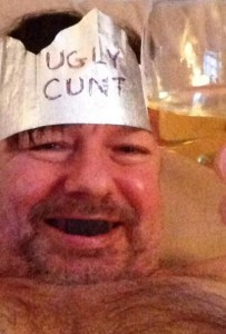 "Gervais submerged in bathtub with blacked out teeth drinking a beer. He is wearing a homemade hat that has ""UGLY CUNT"" scrawled on it."