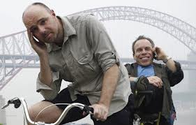 Pilkington and Davis on a bicycle. Warwick is grinning, but Pilkington looks miserable.