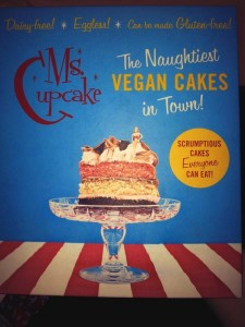 "Cover for ""Ms. Cupcake:  The Naughtiest Vegan Cakes in Town!"" Pictures a piece of cake with a tiny woman in a bikini sitting on top"