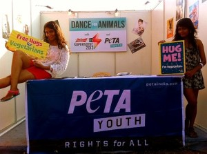 "Two teenagers in mini-dresses pose on a PETA Youth booth offering ""Free hugs"""