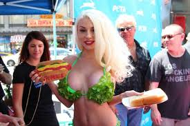 Courtney Stodden poses with a veggie dog in a revealing lettuce bikini. Men in the background stare at her.