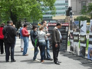 Outdoor display of several animal rights posters with passerby stopped to read them