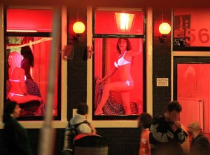 Men walking through red light district with women's bodies in the windows