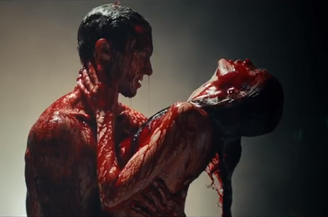 Lead singer Adam Levine holds a reclining woman. Both are naked and covered in blood