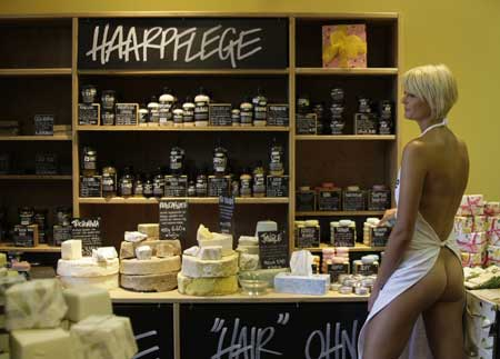 LUSH employee wearing nothing but an apron as part of an advertising campaign