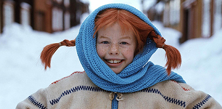 Image of Pippi Longstocking, white, red-haired girl with long braided hair smiling in the snow