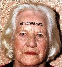 "Closeup of an older woman's face. She has ""BEST BEFORE MAR 73"" printed across her forehead."