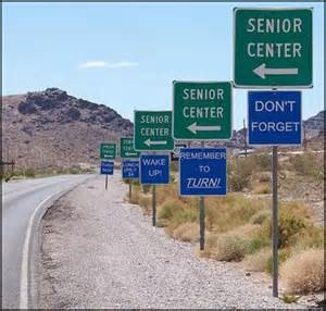 Series of road signs pointing to senior center. Underneath them are another series of signs reminding them to make the turn and not forget.