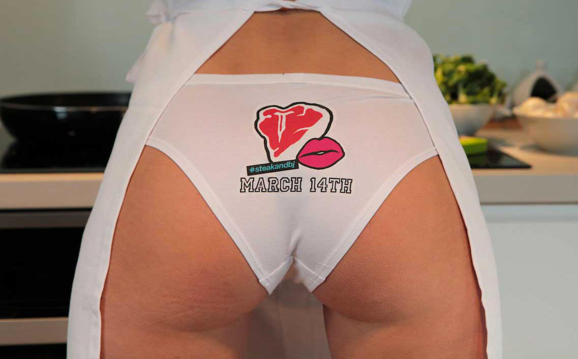 Close up of a woman's bottom, legs spread. She appears to be naked except for an apron and a pair of underwear with the organization's logo printed over the back of the panties. The logo is a cartoon of a steak and a pair of lips.