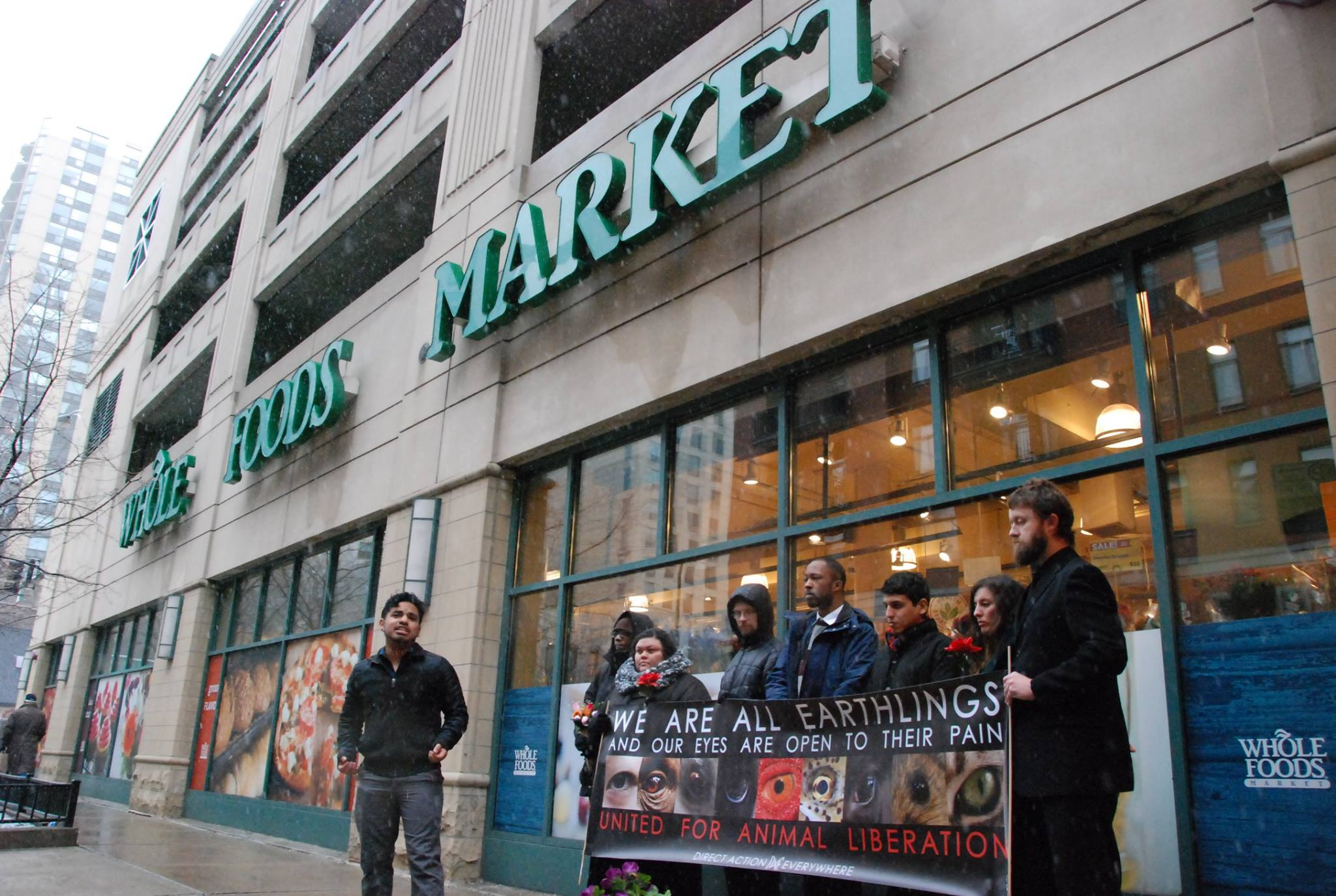 Activists lined up outside of Whole Foods holding an animal rights banner. Man in front of them is yelling the message to the public.