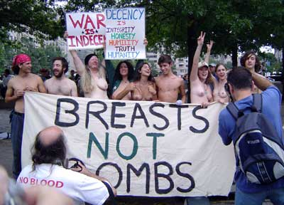 "Protesters (mostly white and middle-aged or older) holding a number of signs, predominantly a banner that reads ""Breasts Not Bombs"""