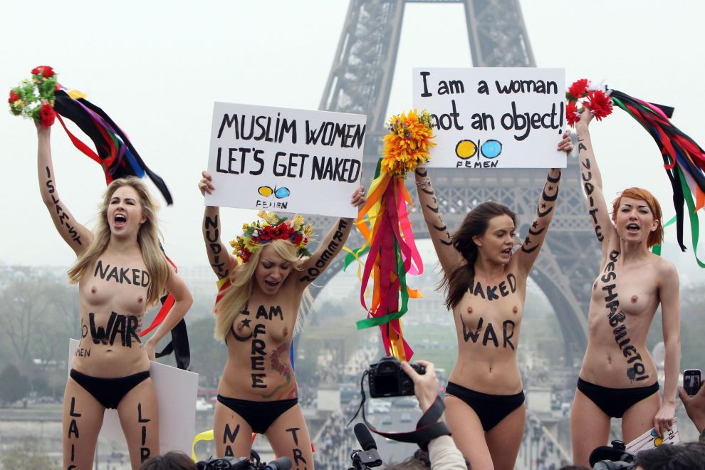 "Four young white thin women wearing only underwear holding signs in front of the Eiffel tower, ""Muslim women, let's get naked,"" and ""I am a woman, not an object"""