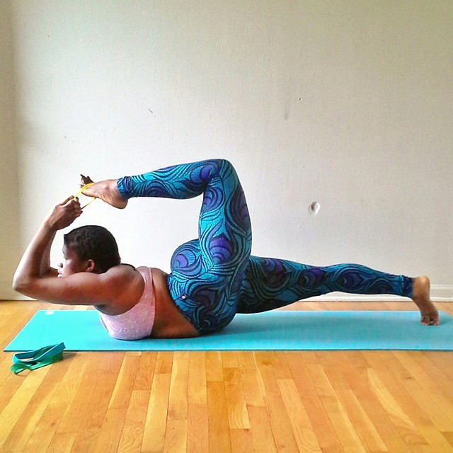 African American woman of size Jessamyn Stanley demonstrates a complex yoga stretch.