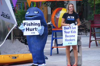 "PETA protest with person in fish suit holding sign that says ""Fishing hurts,"" next to a thin white woman holding a sign that says, ""Don't let your kids become hookers."""