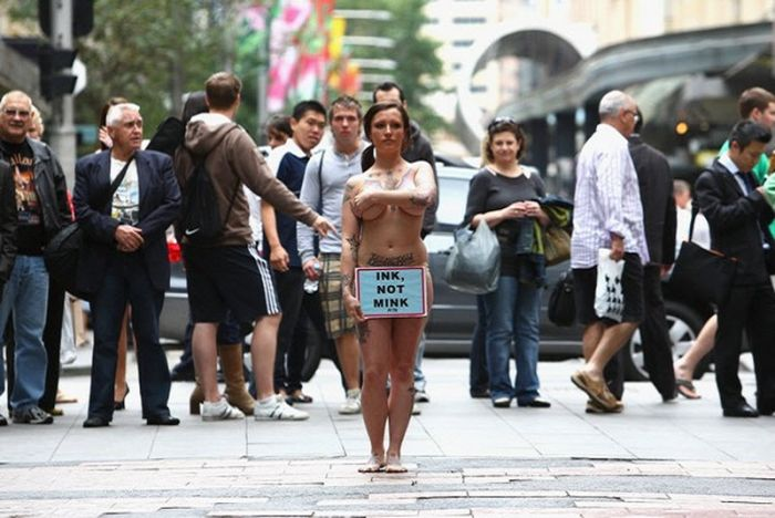 Nude PETA protester (white and female) stands in city street and is surrounded by men