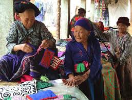 Older Laotian women sewing rugs for market