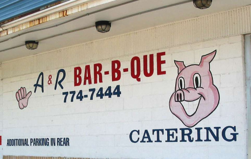 Advert for barbecue catering service with a cartoon pig face that is smiling
