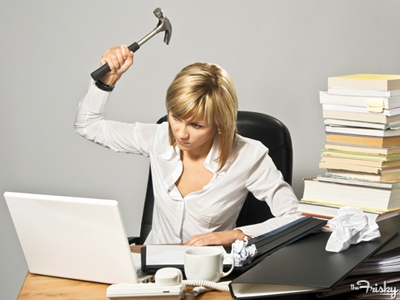 Woman at her desk raising a hammer to her laptop