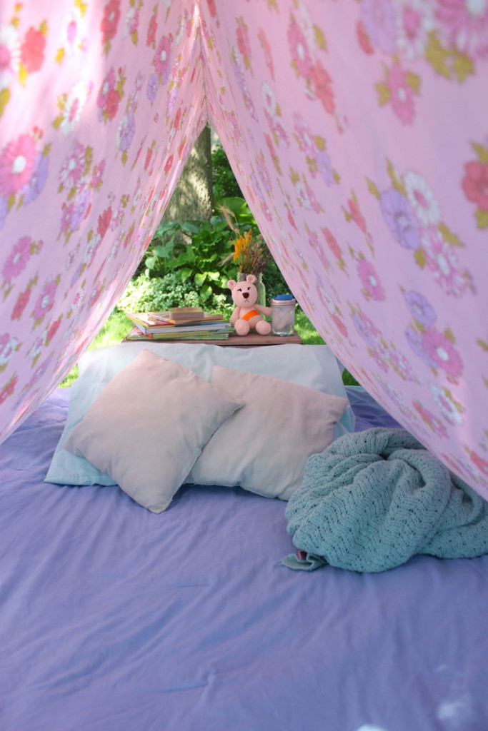 Pink flowery sheet set up as a tent with blankets and pillows inside
