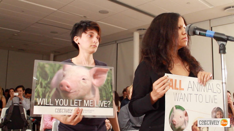 "Author stands at protest holding a poster of a pig that asks, ""Will You Let Me Live?"""