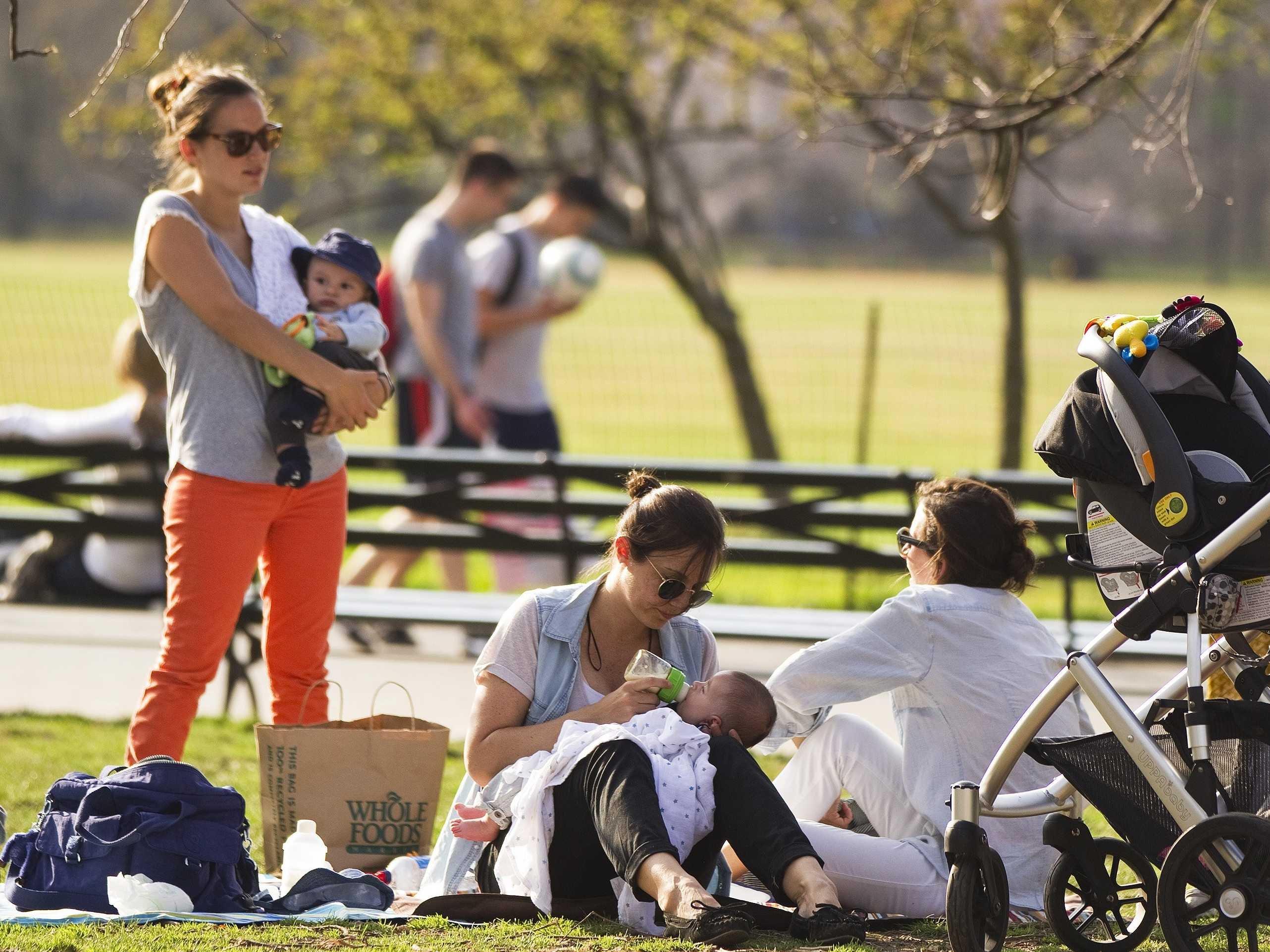 Thin white women in a park tending to children