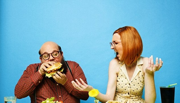Woman looking outraged as her male partner scoffs down a burger