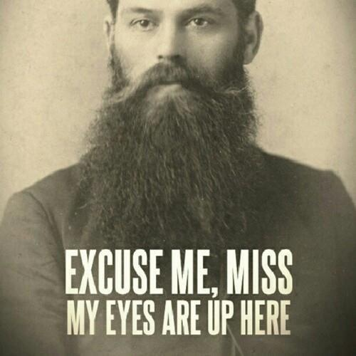 "Large bearded man, reads, ""Excuse me miss, my eyes are up here"""
