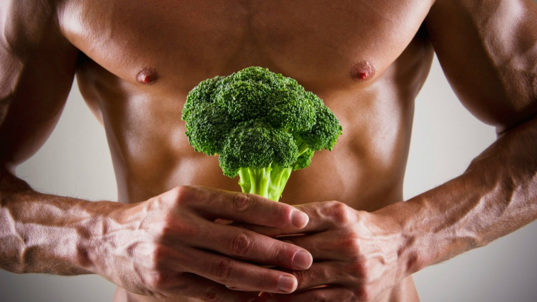 Muscled man's chest and arms, holding large floret of broccoli