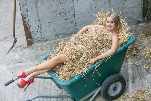 Young white woman naked in a wheel barrow; she is covered in hay and wearing very large pump red heels