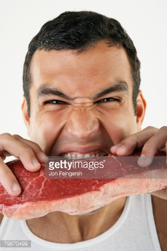 Man gnawing on raw steak