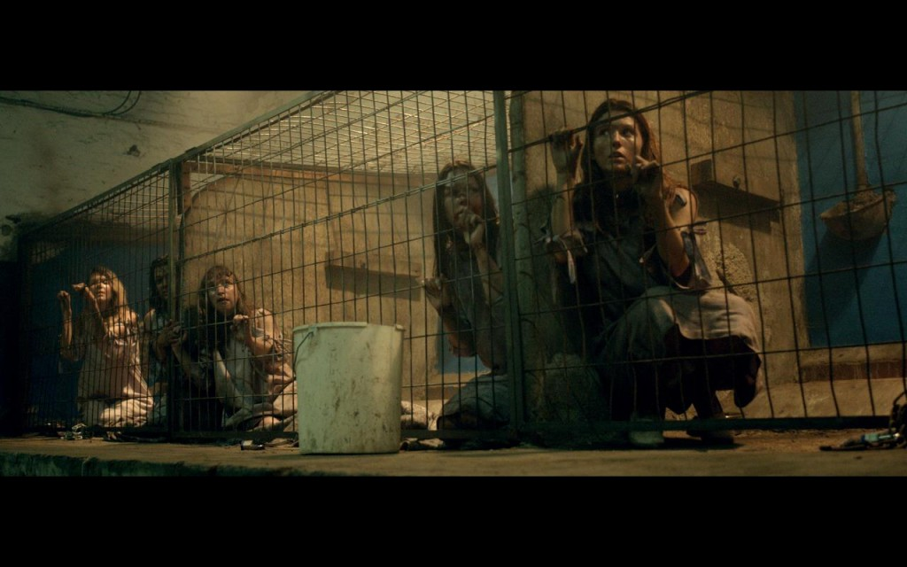 "Women crouch in filthy cages, dressed in rags, looking around in fear; promo image for ""The Herd"""