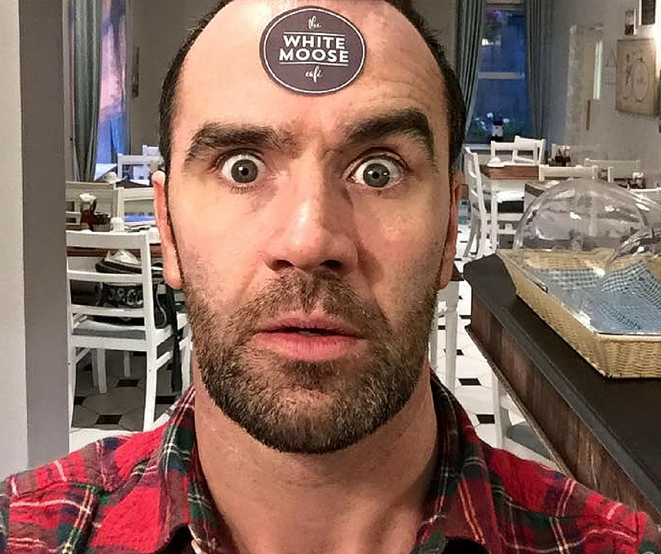 """Photo of owner from White Moose Cafe Facebook page. Caption reads, """"If you do happen to see Paul in the café, it is strongly advised that you do not approach him with any complaints. This is in the interest of your own safety, as well as the safety of others around you."""""""