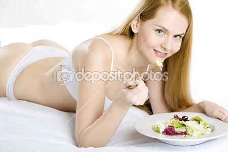 Mujer acostada en la cama con ropa interior blanca comiéndose una ensalada.
