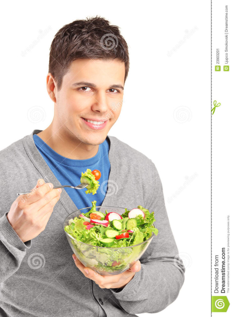 Man about to eat a forkfull of salad, smiles softly to camera