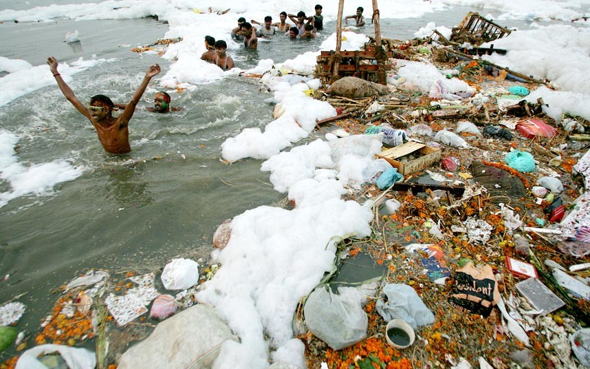 Devotees wade in the Yamuna River, which froths heavily with pollution and is littered with trash