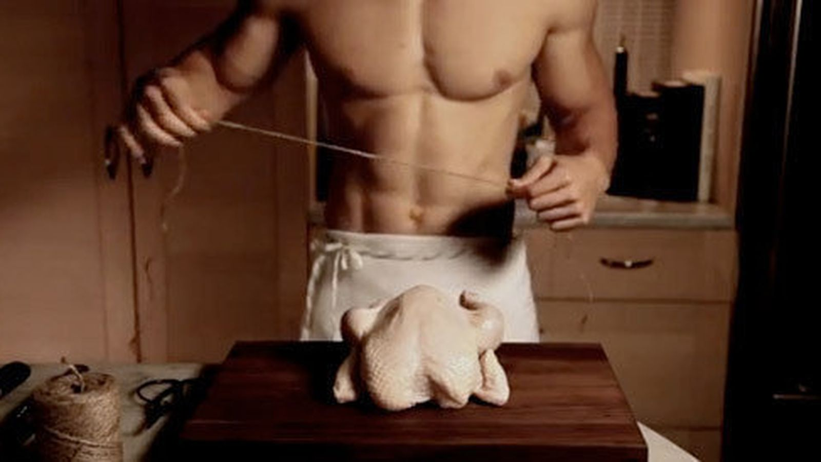 Shirtless, heavily-muscled man prepares to bind a chicken's corpse on a cutting board