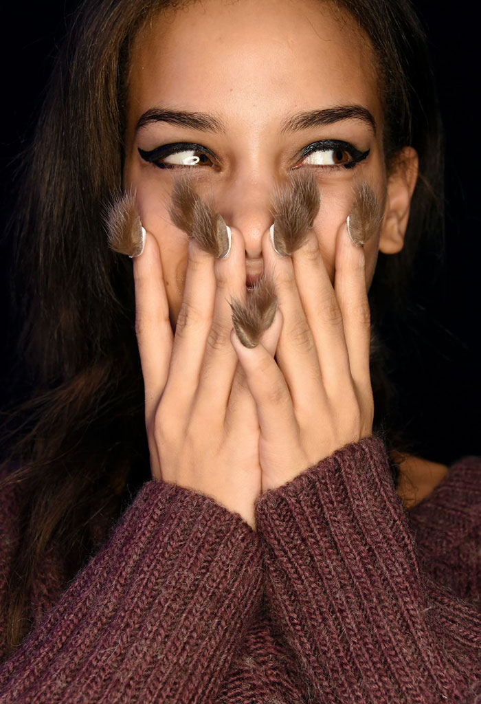 Woman covers her face with her hads, has tufts of brown fur glued to her nails