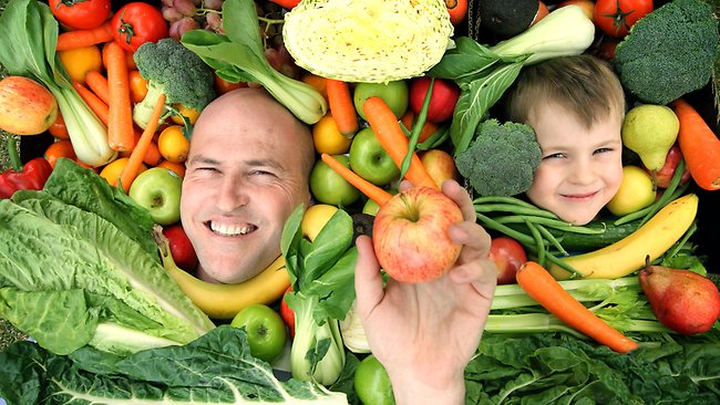 A father and son in a sea of fruit and vegetables, only their faces are peaking out