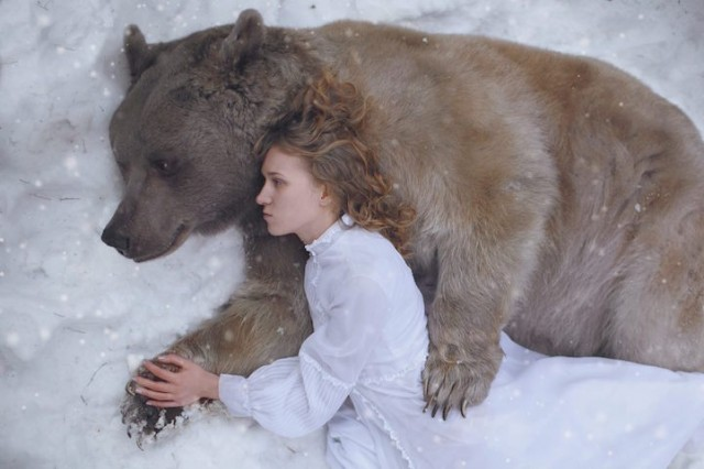 Woman lying in snow with a bear