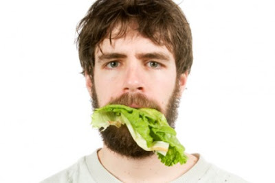 Man with big lettuce leaf hanging out of mouth