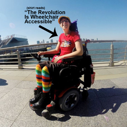 "Photo of myself in my motorized wheelchair, Betty. It am outdoors on a sunny day at the piers in New York City. I am dressed colorfully with colorful striped socks, black combat boots and capris and a red t-shirt that reads ""The Revolution Is Wheelchair Accessible."""